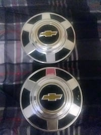 Two 1970s Chevy truck hubcaps
