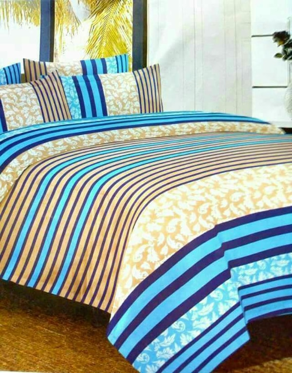blue, yellow, and brown floral stripe bedspread