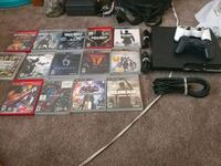 black Sony PS3 console with controllers and game cases