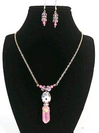 Gold colored necklace with pink crystatl pendant