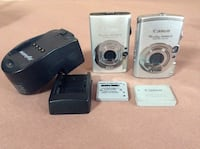 Two silver canon power shot digital camera;black battery charger