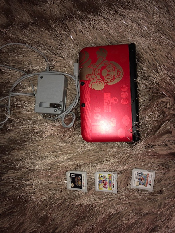 red Nintendo 3DS with game cartridges