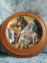 round brown wooden framed painting of Native American with horse