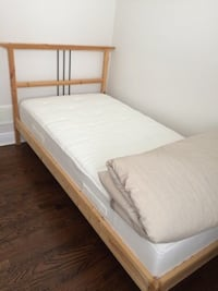 White mattress and brown wooden bed frame