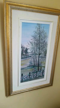 trees and houses painting with brown wooden frame
